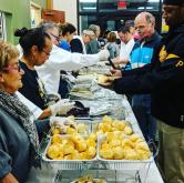 Volunteers help with the serving line.